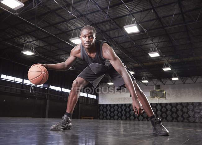 Портрет уверенный молодой баскетболист капает мяч на корте в спортзале — стоковое фото