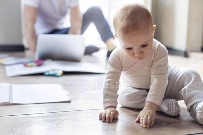 Bambino figlia seduta sul pavimento vicino al padre che lavora al computer portatile — Foto stock