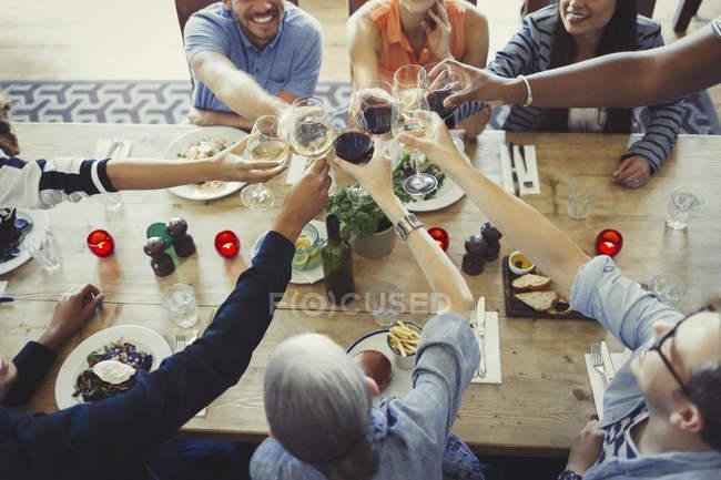 Visão aérea amigos brindar copos de vinho na mesa do restaurante — Fotografia de Stock