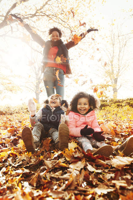 Playful mother and daughters throwing autumn leaves in sunny park — Stock Photo