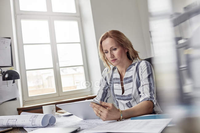 Female architect using digital tablet in office with blueprints — Stock Photo