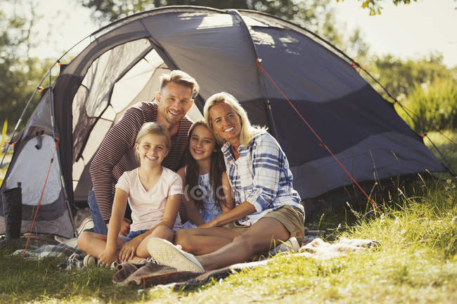 Portrait smiling family relaxing outside sunny campsite tent — Stock Photo