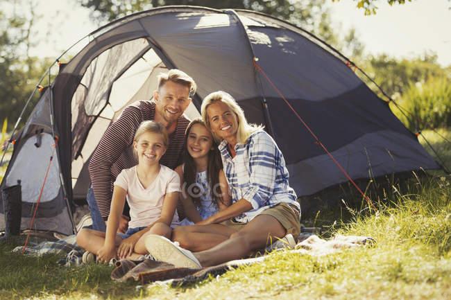 Портрет посміхаючись сім'ї розслабляючий за межами Сонячний кемпінгу намет — стокове фото