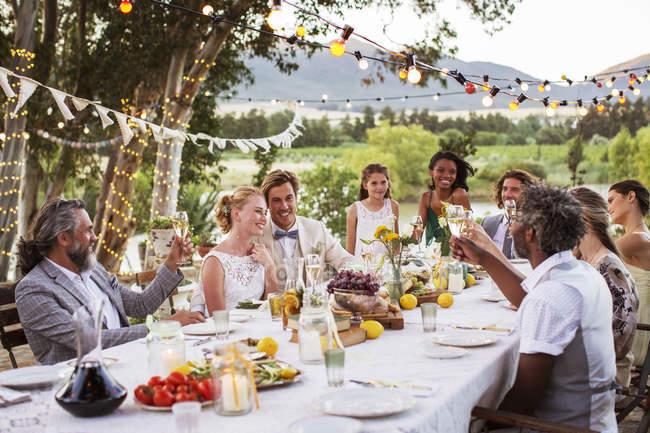 Молодої пари і їх гостей, сидячи за столом під час весілля прийом в саду — стокове фото