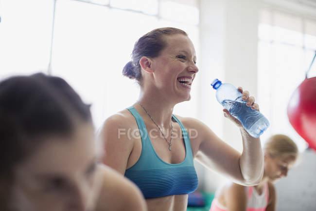 Смеющаяся женщина пьет воду и отдыхает после тренировки в спортзале — стоковое фото