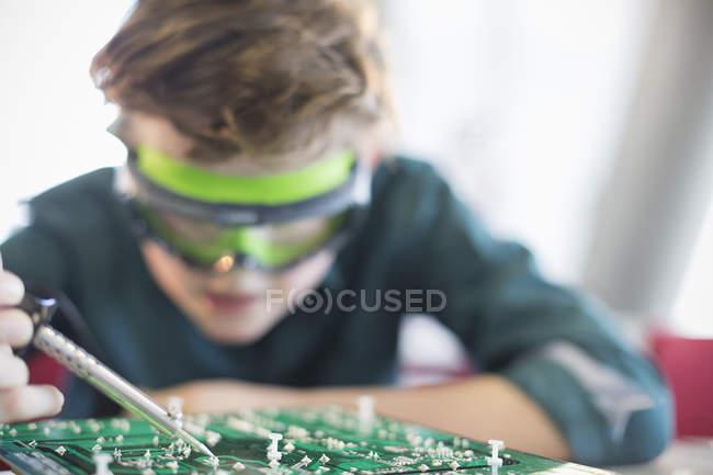 Concentrati allievo del ragazzo per saldatura del circuito in aula — Foto stock