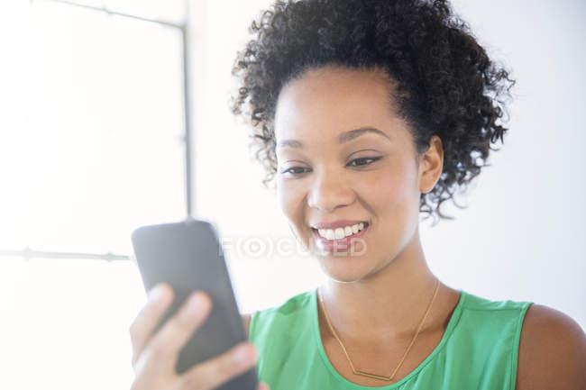 Porträt einer Frau mit schwarzem lockigem Haar, die ihr Handy in der Hand hält — Stockfoto