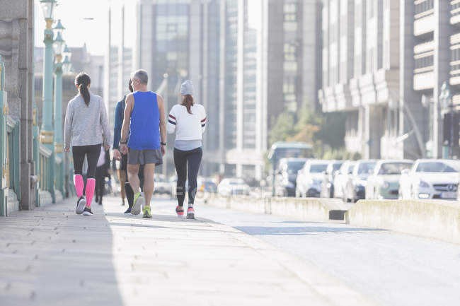 Runners walking on sunny urban city sidewalk — Stock Photo