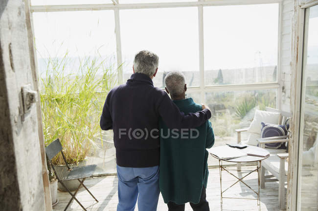 Affectionate senior couple enjoying beach view on sun porch — Stock Photo