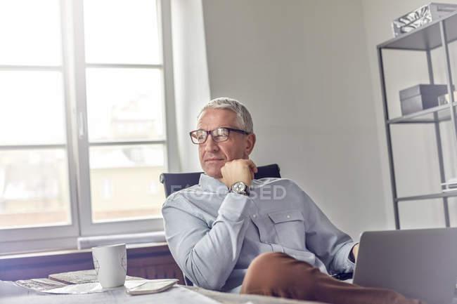 Uomo d'affari fiducioso e pensieroso con laptop che distoglie lo sguardo in ufficio — Foto stock