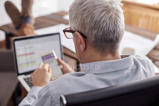 Empresário, trabalhando, usando o telefone celular e laptop no escritório — Fotografia de Stock