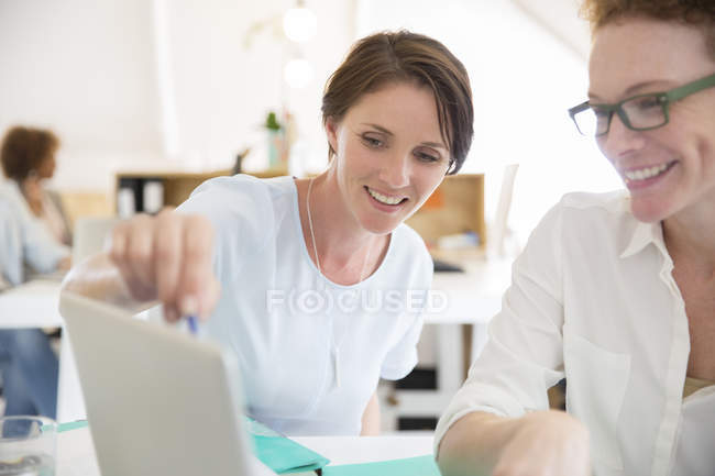 Women using laptop in office and smiling — Stock Photo