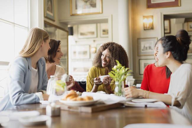 Donne sorridenti che bevono caffè e parlano al tavolo del ristorante — Foto stock