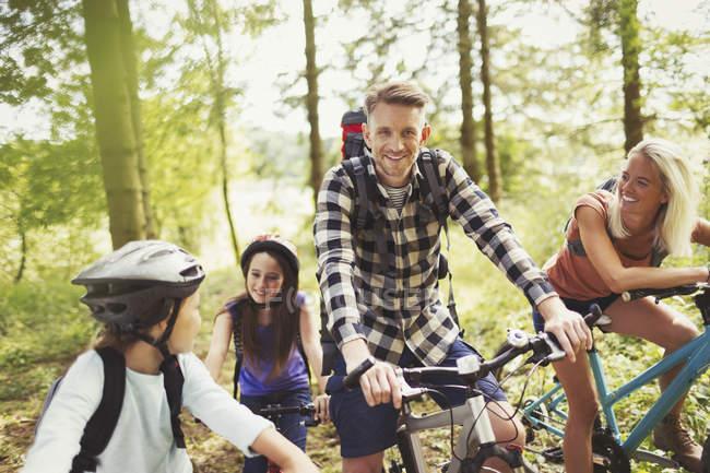Smiling family mountain biking in woods — Stock Photo
