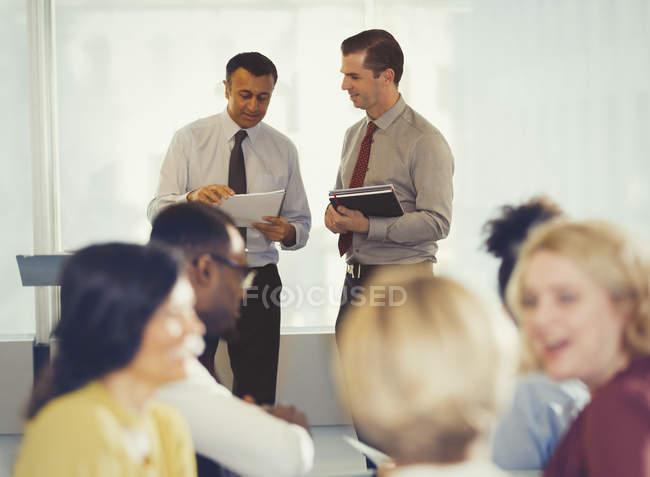 Empresarios discutiendo papeleo en conferencia - foto de stock