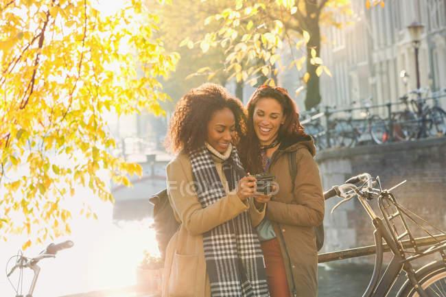 Улыбающиеся молодые женщины-друзья с цифровой камерой вдоль солнечного городского осеннего канала, Амстердам — стоковое фото