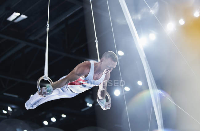 Male gymnast performing on gymnastics rings in arena — Stock Photo