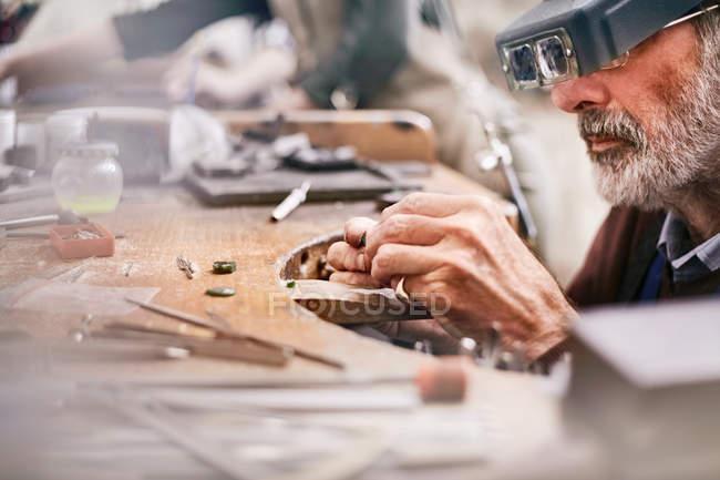 Male jeweler using headband magnifier making jewelry in workshop — Stock Photo