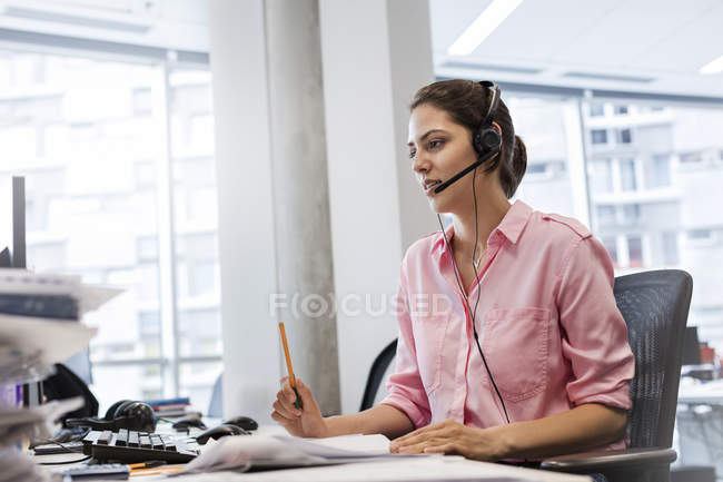 Businesswoman with hands-free device talking on telephone at office desk — Stock Photo