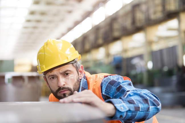 Serious steel worker examining steel in factory — Stock Photo