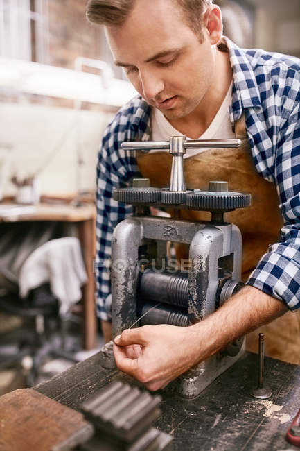 Male jeweler using equipment in workshop — Stock Photo