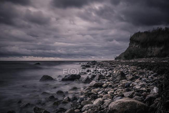 Tranquil rocks on ocean beach below stormy, overcast clouds, Bisserup, Denmark - foto de stock