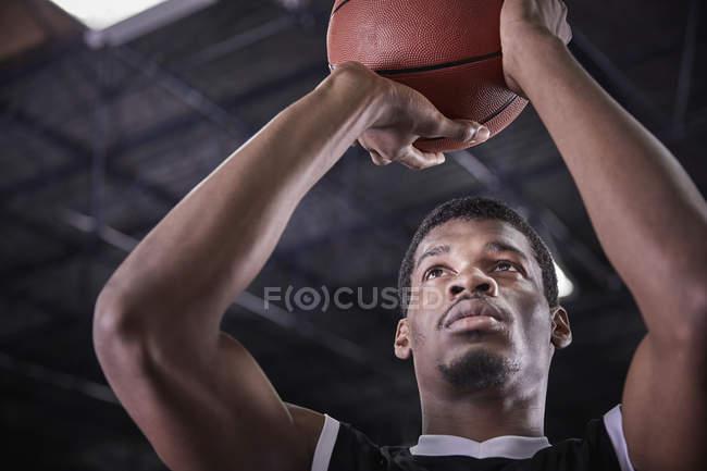 Сосредоточенный молодой баскетболист, стреляющий свободным броском — стоковое фото
