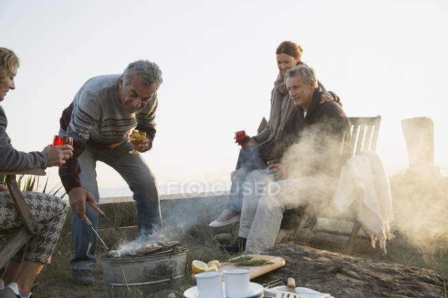 Mature couples barbecuing and drinking wine on sunset beach — Stock Photo