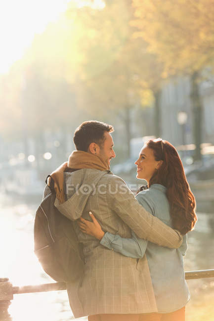Smiling young couple hugging on sunny autumn bridge over canal — Stock Photo