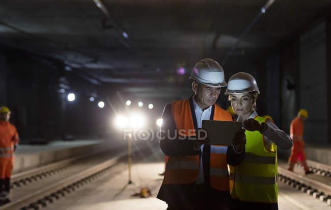 Foreman e trabalhador da construção civil usando tablet digital no canteiro de obras subterrâneas escuras — Fotografia de Stock