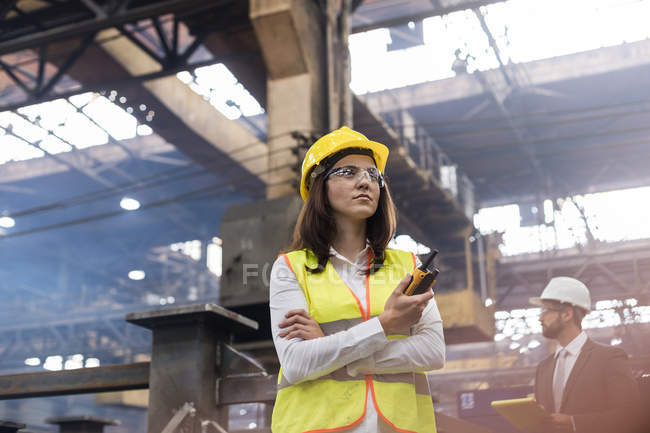 Female steel worker with walkie-talkie in factory — Stock Photo