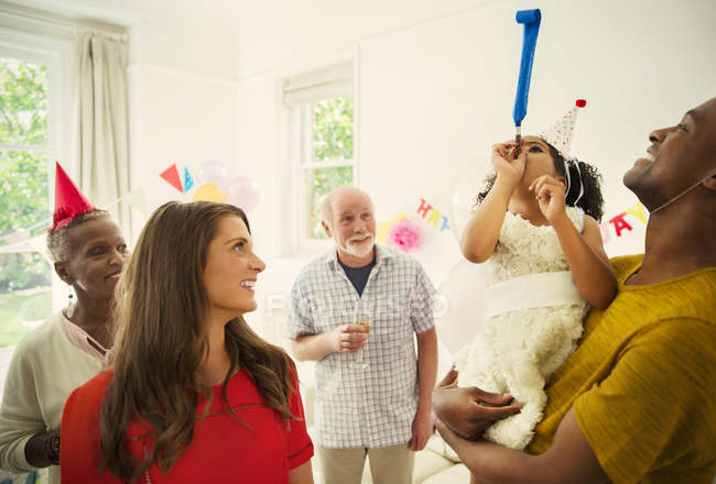 Multi-ethnic family celebrating with party favors — Stock Photo
