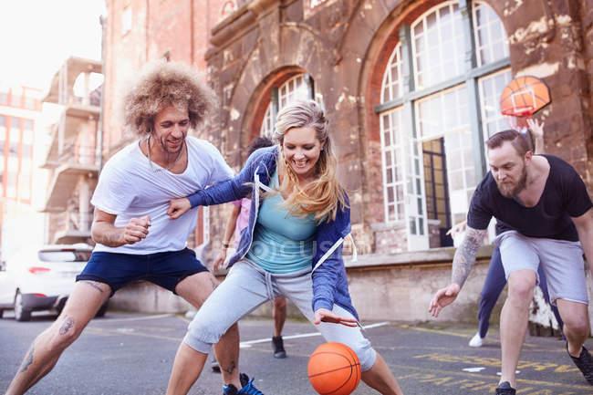 Amigos jugando baloncesto en cancha de baloncesto urbana - foto de stock