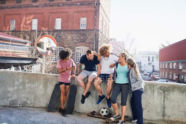 Amici con skateboards hanging out sulla parete urbana estate — Foto stock