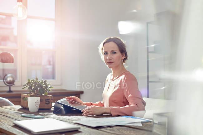 Ritratto donna d'affari sicura che utilizza tablet digitale alla scrivania in ufficio — Foto stock