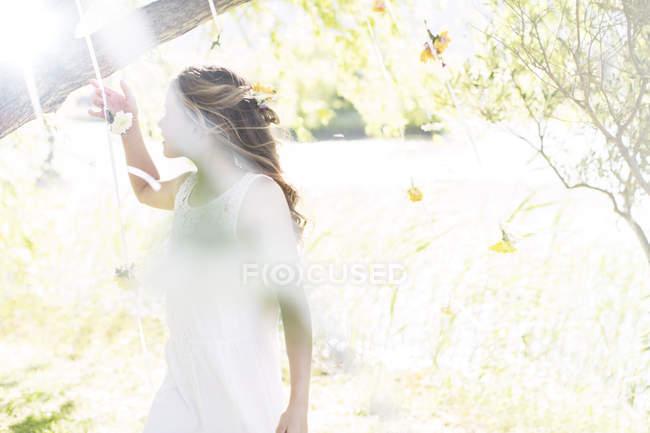 Подружка невесты играет с украшениями в саду во время свадебного приема — стоковое фото