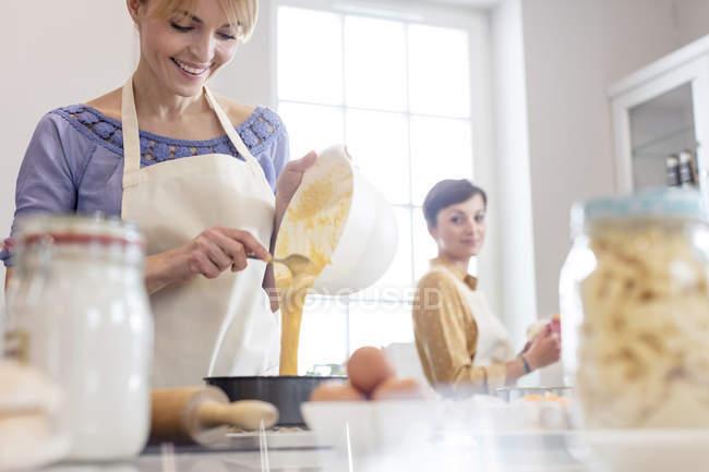 Traiteurs femelles cuisson, verser la pâte à gâteau dans l'étain dans la cuisine — Photo de stock