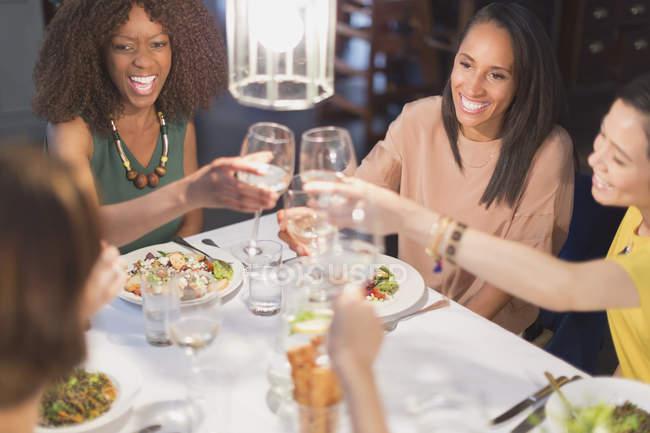 Mujeres sonrientes amigas brindando por copas de vino blanco cenando en la mesa del restaurante - foto de stock