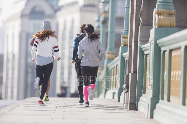 Бегуны по солнечному городскому тротуару — стоковое фото