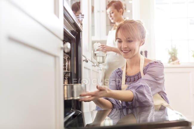 Femme souriante cuisson, placer le gâteau au four — Photo de stock