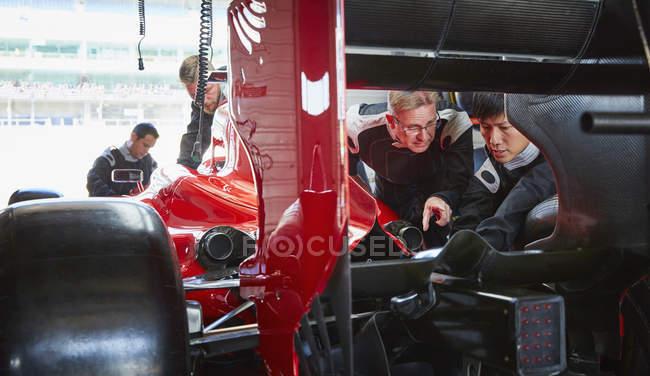 Pit crew mechanics examining race car in repair garage — стокове фото