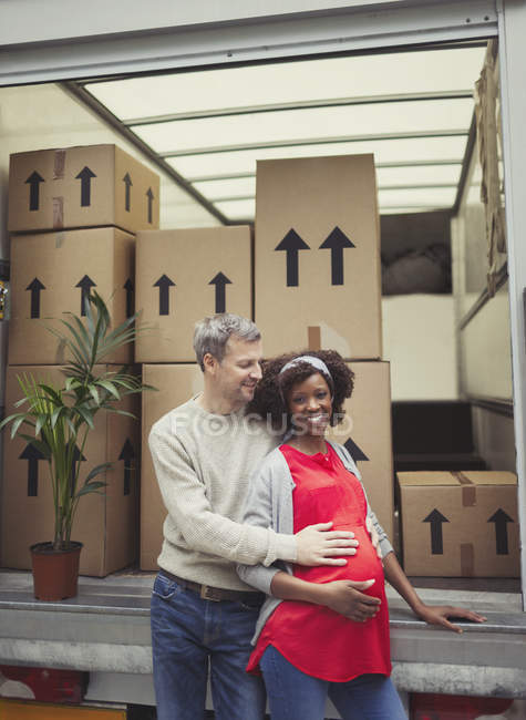 Portrait smiling pregnant multi-ethnic couple at moving van — Stock Photo