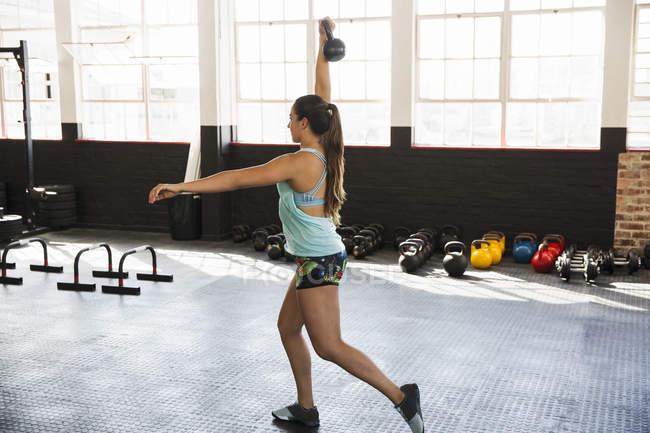 Junge Frau üben Ausfallschritte mit Kettlebell in Turnhalle — Stockfoto