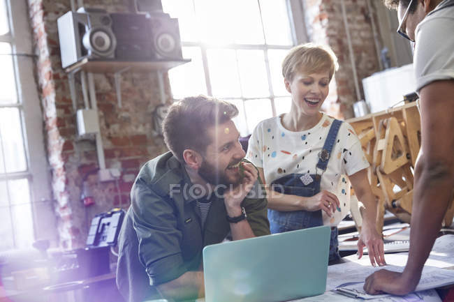 Smiling designers meeting at laptop in workshop — Stock Photo