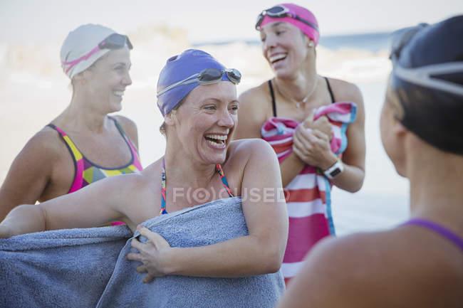 Nageurs actives féminines avec des serviettes au rivage de l'océan à l'extérieur — Photo de stock
