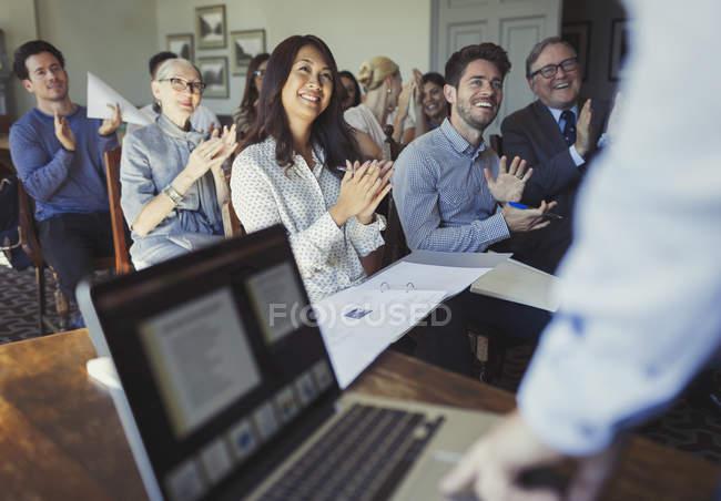 Улыбающиеся бизнесмены аплодируют ведущему бизнесмену за презентацией конференции на ноутбуке — стоковое фото