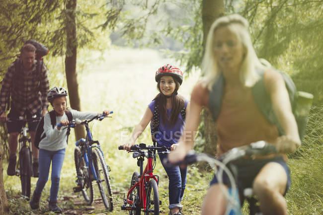 Family mountain biking in woods — Stock Photo