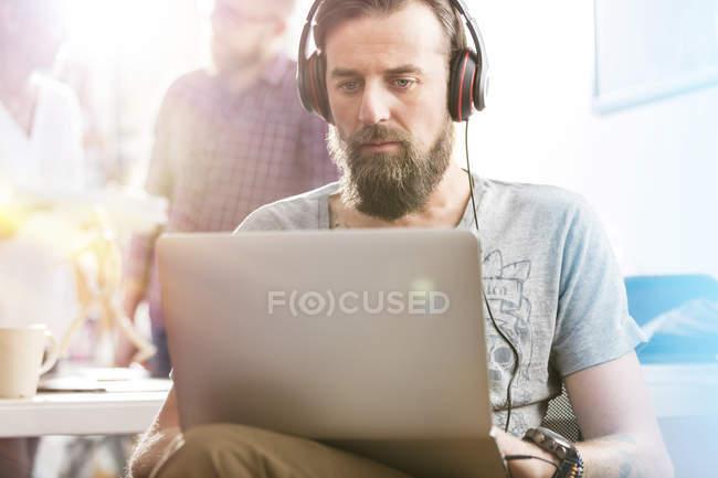 Sérieux professionnel de la conception masculine avec écouteurs utilisant un ordinateur portable dans le bureau — Photo de stock