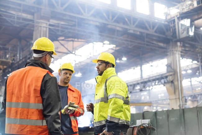 Сталеві працівників говорити в заводу на роботі — стокове фото