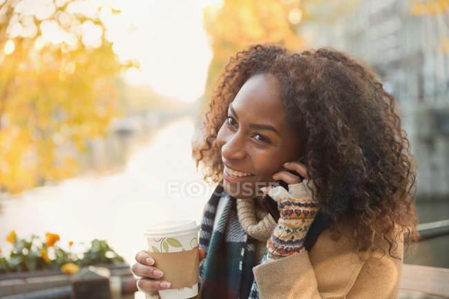 Souriant jeune femme boire du café et parler sur le téléphone cellulaire au café trottoir automne — Photo de stock